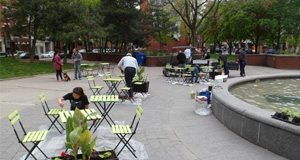 Friends of Berczy Park volunteers paint outdoor furniture