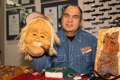 Talented wood carver Arnold Koch displays a very cool wooden mask he carved for Halloween. Photo by Shelly Cameron